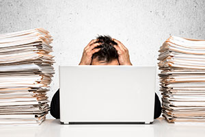 Photo of worker at desk surrounded by paper